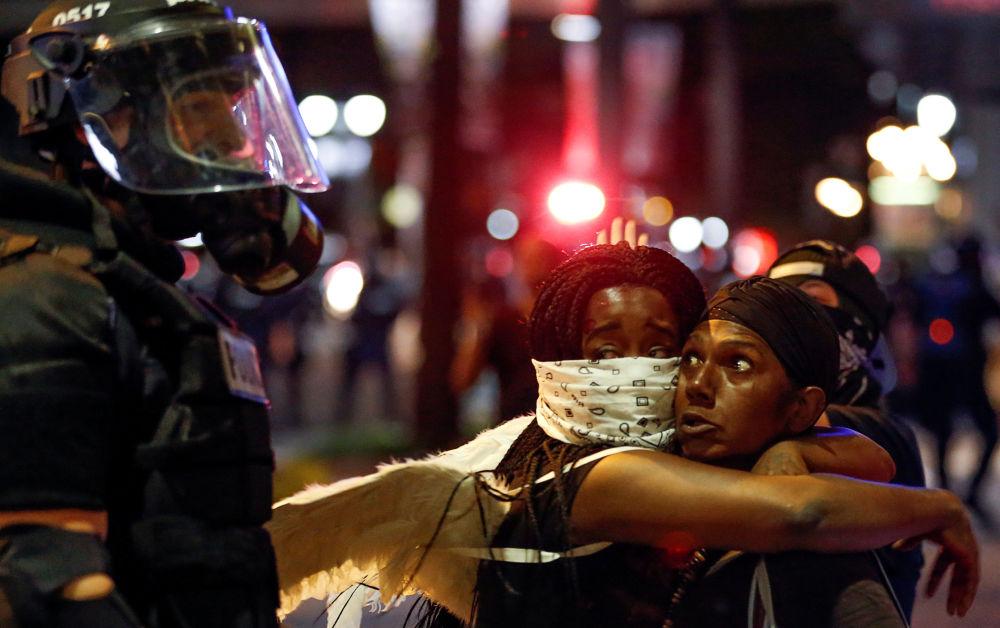 Dvě ženy se objímají před policistou během protestů v americkém Charlotte