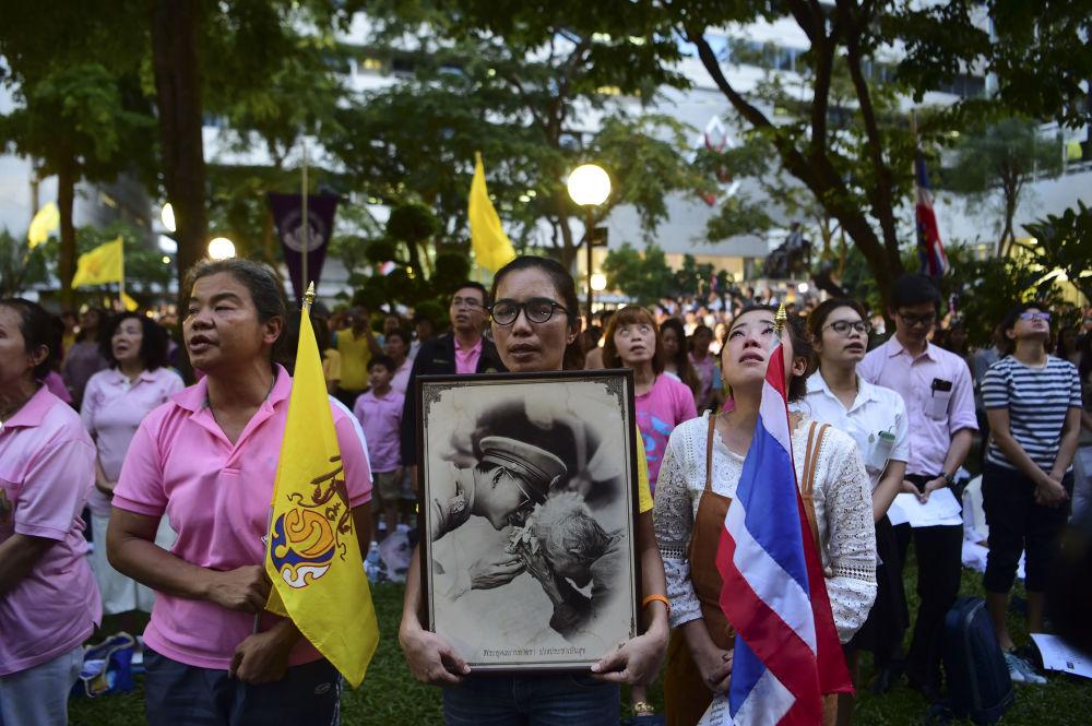 Lidé s portréty thajského krále Pchúmipchona Adundéta před nemocnicí v Bankoku, kde byl král hospitalizován