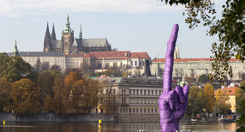 Zdvižený prostředník na pozadí Pražského hradu