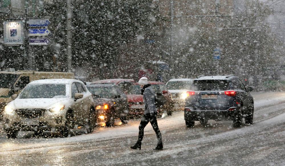 Žena přechází ulici za vánice v Krasnojarsku