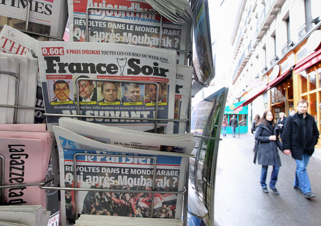 People are seen walking behind French daily newspapers displayed at a news kiosk in Paris. (File)