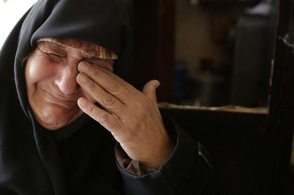 Žena pláče po návratu do vyloupeného domu v Aleppu