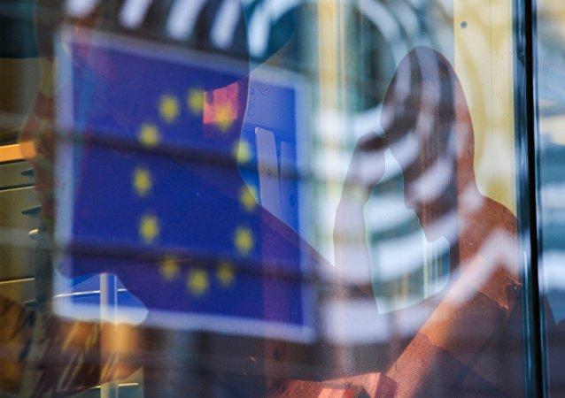 Odraz vlajky EU v okně budovy v Bruselu