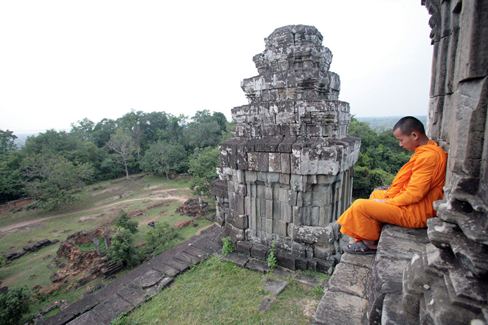 A young buddhist monk reads on the stairs of Phnom Bakheng temple near the Temple of Angkor 22 November 2007, near siem Reap, Cambodia