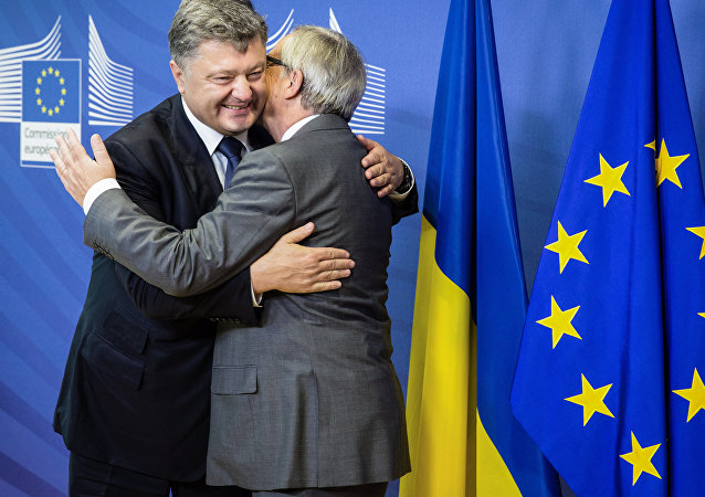 This handout picture taken and released by the Ukrainian presidential press-service shows President of the European Commission Jean-Claude Juncker (R) and Ukrainian President Petro Poroshenko embracing prior their talks in Brussels on August 27, 2015.