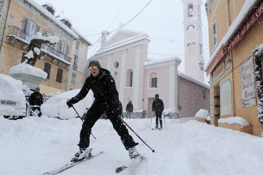 Muži na lyžích na ulicích komuny Corte na francouzském středomořském ostrovu Korsice