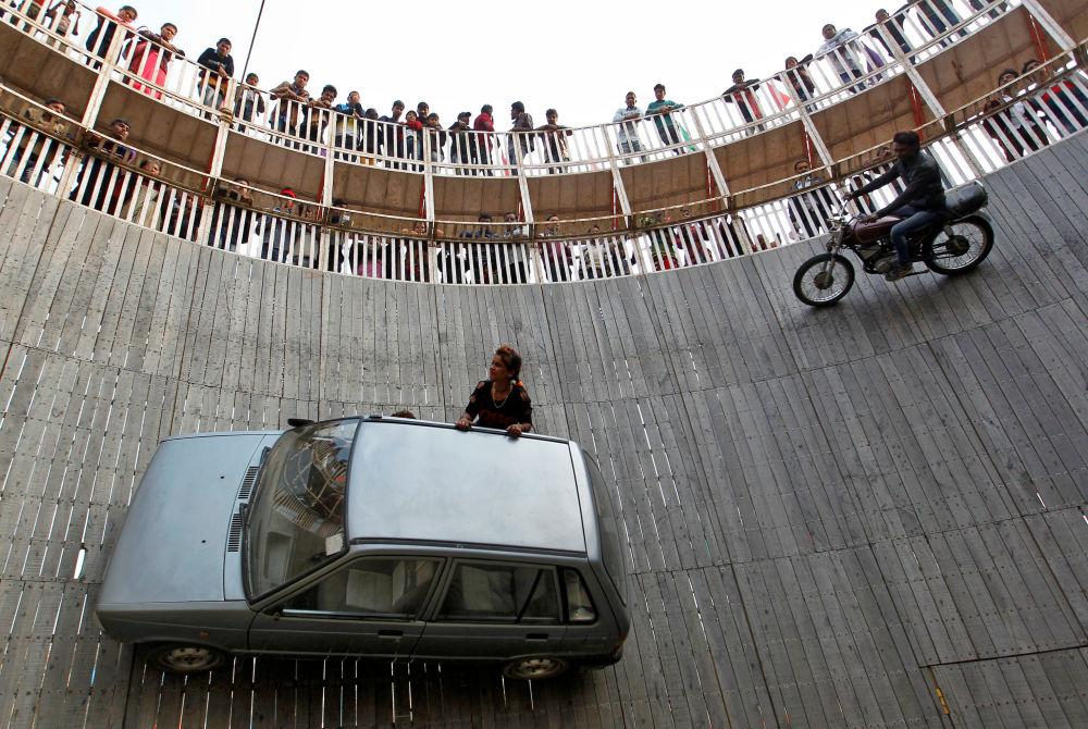 Kaskadéři vykonávají trik Studna smrti na výstavě v Allahabadu, Indie