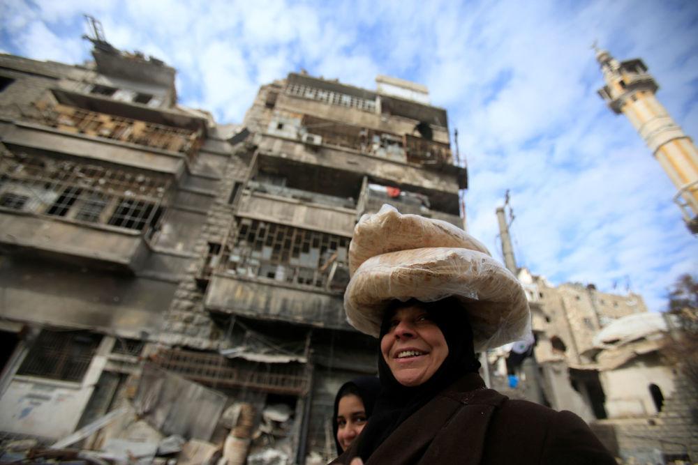 Žena nese chléb ve zničené čtvrti Aleppa