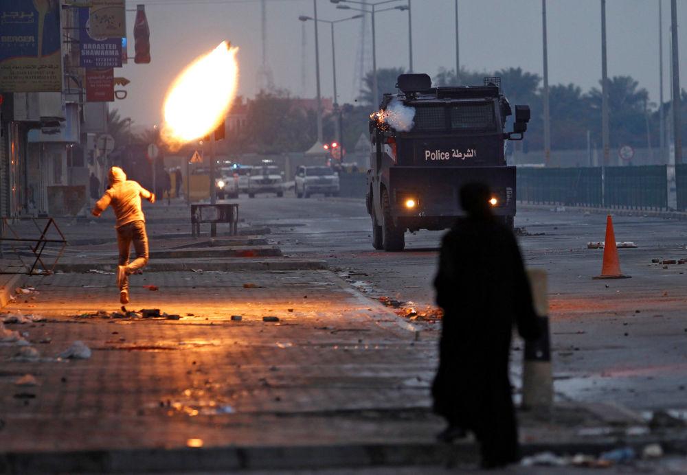 Demonstrant hází láhev se zápalnou směsí během protestů v Bahrajnu