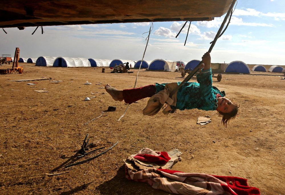 Holčička na houpačce v běženeckém táboru na jihovýchodě Mosulu