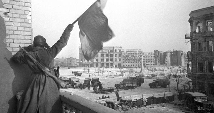 Rudá vlajka nad náměstím Padlých bojovníků v osvobozeném Stalingradu. Na pozadí je budova obchodního domu, kde byl zajat štáb 6. armády Wehrmachtu v čele s polním maršálem Paulusem