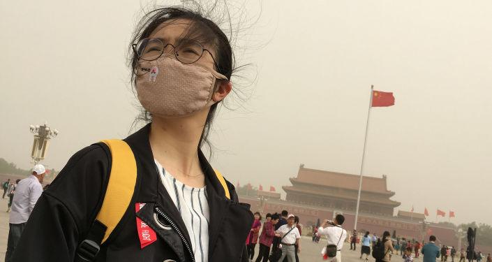 Dívka v masce proti smogu na náměstí Tchien-an-men v centru Pekingu