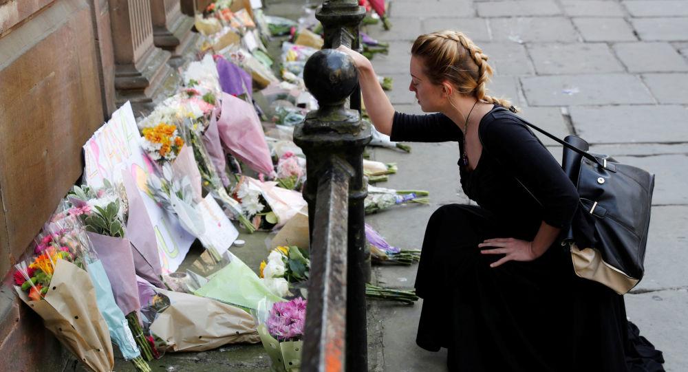 Dívka vedle květin k uctění památky zemřelých při útoku v Manchesteru