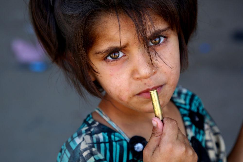 Děvčátko s nábojem v ruce nedaleko syrské Rakky