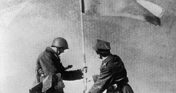 Sovětský a polský voják během vztyčování vlajky. 1945.
