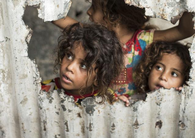 Palestinské děti koukají skrze díru v plotě. Ilustrační foto