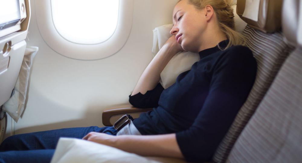 Dívka spící na palubě letadla