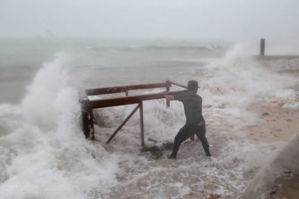 Muž se pokouší dostat z oceánu stůl, který moře odneslo z restaurace během uragánu Maria v Punta Cana, Dominikánská republika