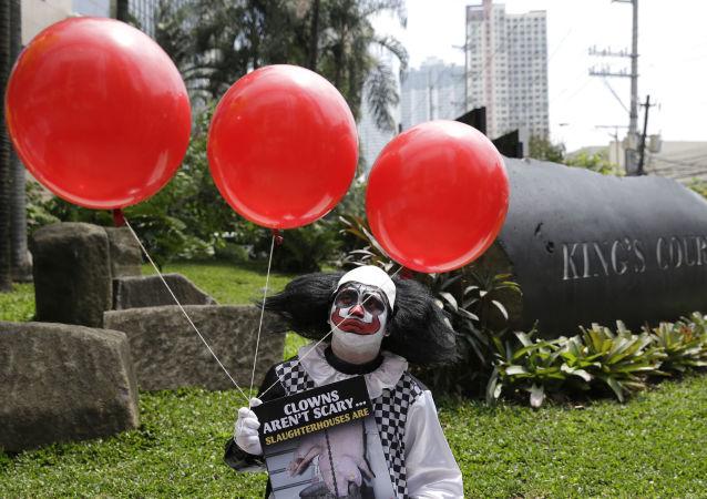 Klaun s rudými balónky se účastní demonstrace na stanici metra v Manile