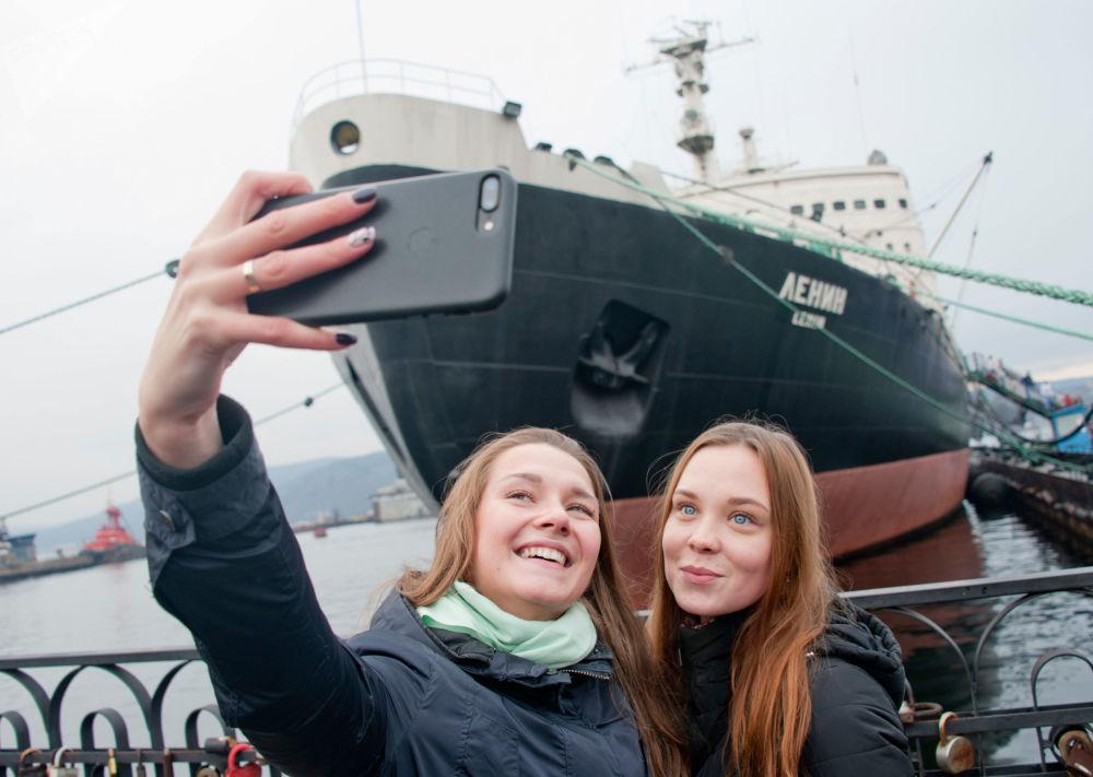 Dívky se fotografují před muzeem-ledoborcem Lenin v Murmansku