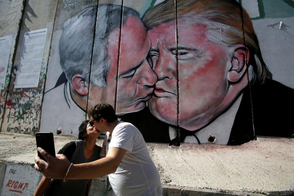 Turisté se fotografují před graffiti se zobrazením polibku izraelského premiéra Benjamina Netanjahua a prezidenta USA Donalda Trumpa na zdi v Betlému, Palestina