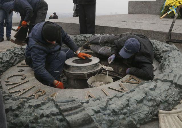 Pracovníci likvidují následky vandalismu v Parku Věčné slávy v Kyjevě