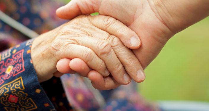Ruka staré ženy v ruce muže