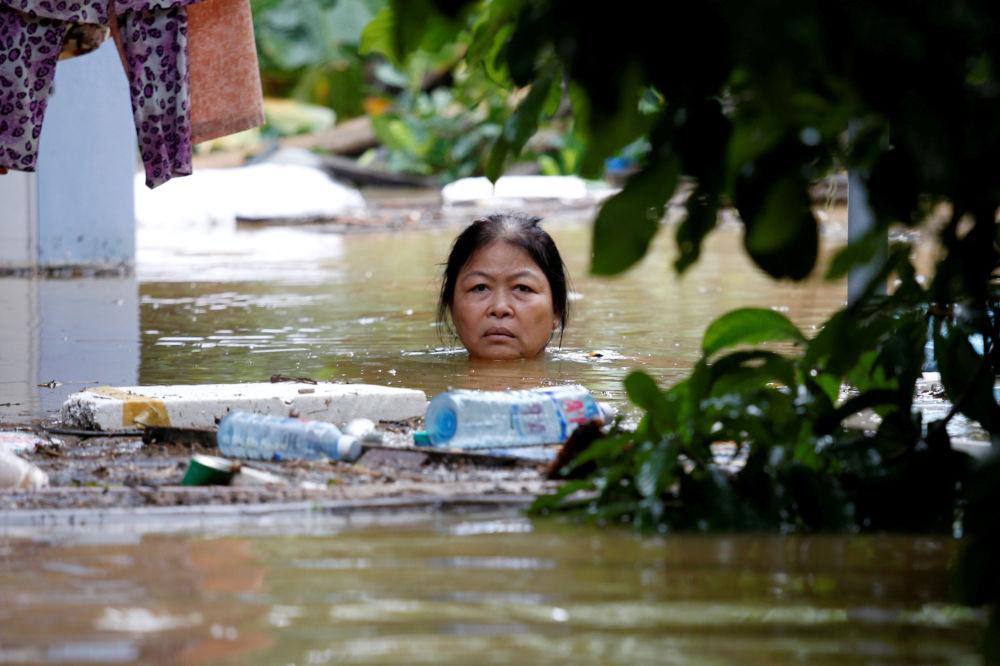 Žena na zaplavené ulici ve vietnamském městě Hội An zařazeném do seznamu UNESCO