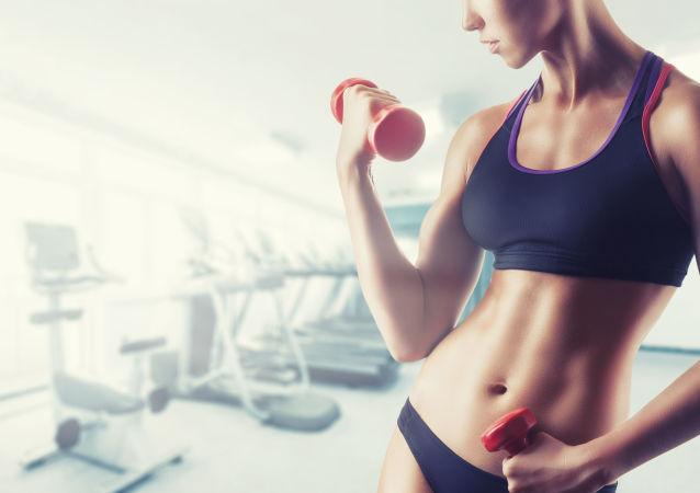 Mladá žena cvičí ve fitku