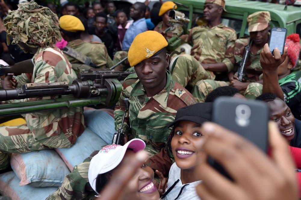 Dívky se fotografují s vojákem Zimbabwe během pochodu za odstoupení prezidenta v Harare