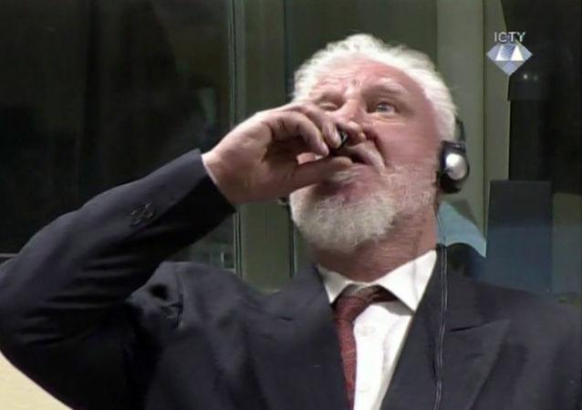 Jeden z vojenských velitelů bosenských Chorvatů, generál Slobodan Praljak, pije jed při zveřejnění odsouzení na zasedání tribunálu v Haagu