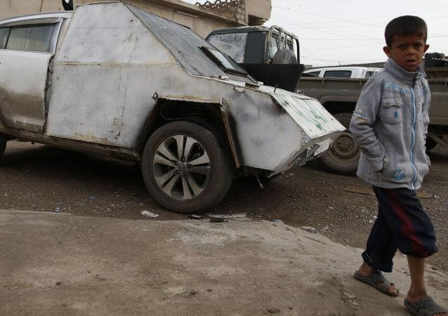 Chlapec u obrněného auta v Iráku
