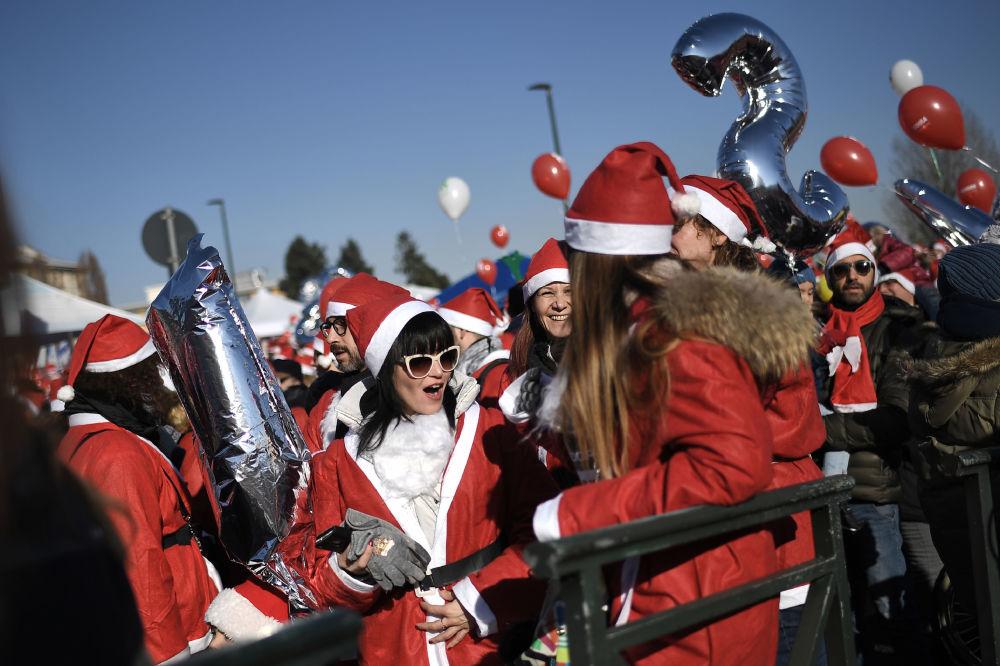 Lidé v kostýmech Santa Klaus v Turínu