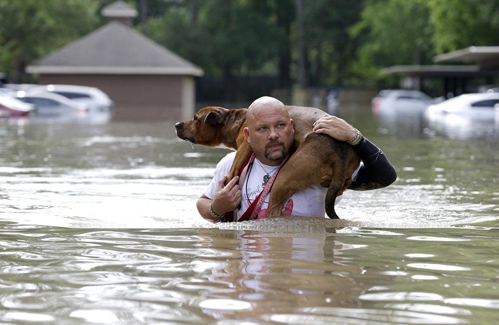 Muž nese na zádech psa při povodni v Houstonu