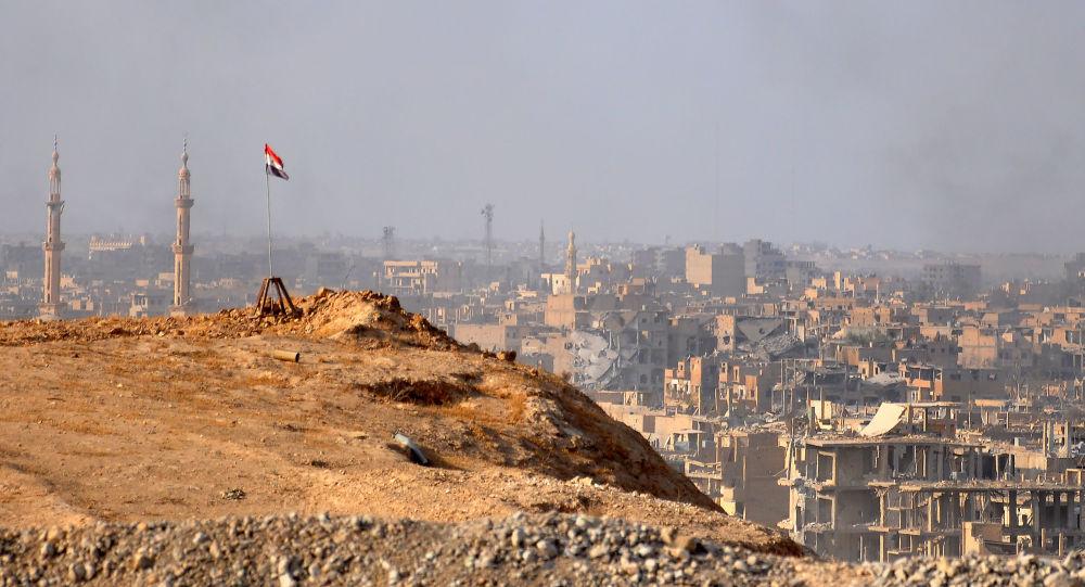 Syrská vlajka na pozadí města Dajr az-Zaur