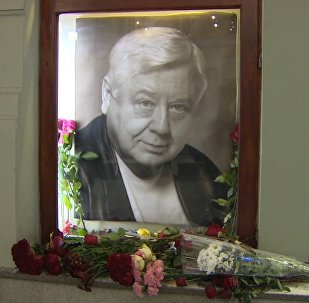 Lidé přinášejí květiny k divadlu, aby uctili památku Tabakova