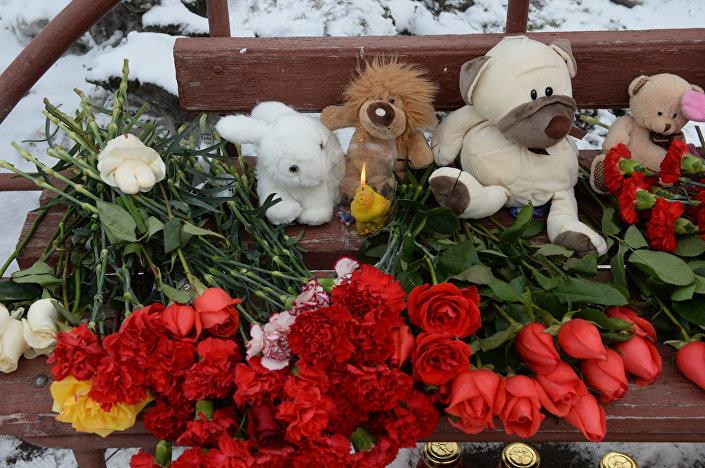 Květiny, svíce a hračky u budovy požárem zničeného obchodního centra