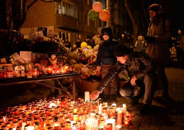 Lidé zapalují svíce na památku obětí v Kemerovu