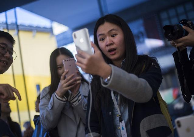 Zákazníci v Pekingu si prohlížejí iPhone