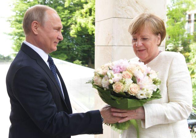 Vladimir Putin daruje květiny kancléřce Angele Merkelové