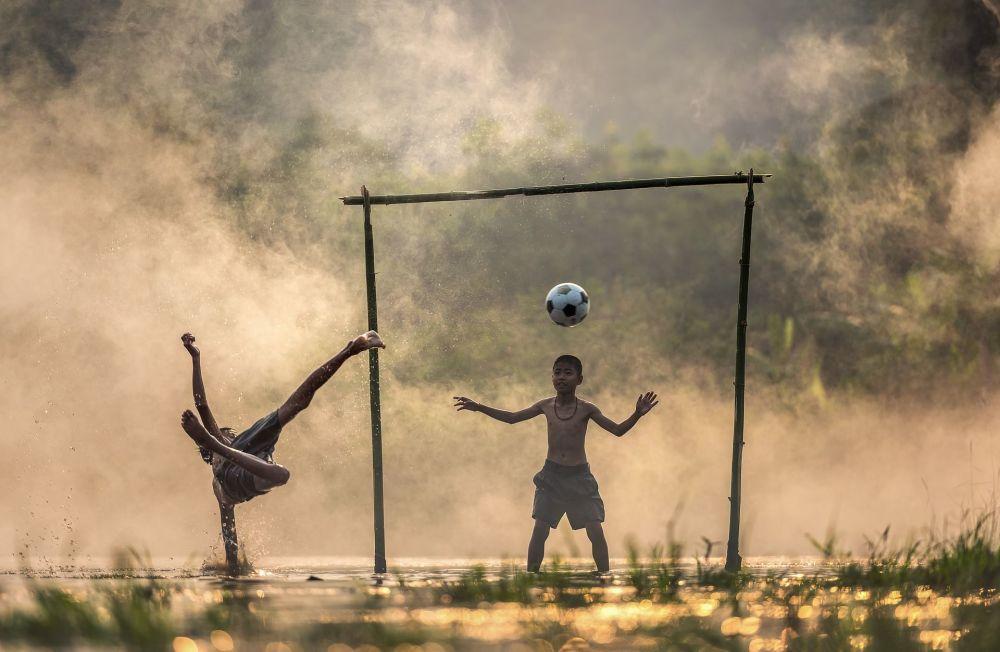 Asijští chlapci si hrají fotbal na venkově