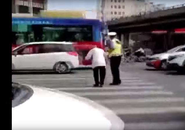 Čínský policista převedl důchodce přes ulici na zádech