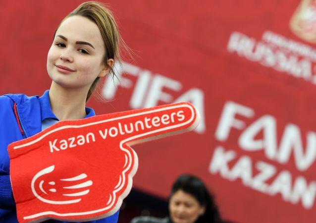 Dobrovolník festivalu fanoušků Světového poháru 2018 v parku fanoušků na nábřeží řeky Kazanka v Kazaňi