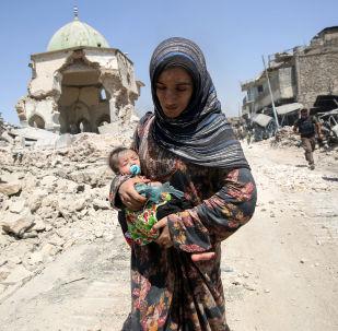 Irácká žena s dítětem před zničenou mešitou Al-Nuri v Mosulu v červenci 2017