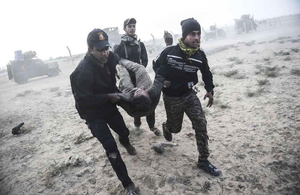 Členové irácké protiteroristické služby nesou zraněného kamaráda během střetů s teroristy z ISIS na okraji Mosulu, říjen 2016