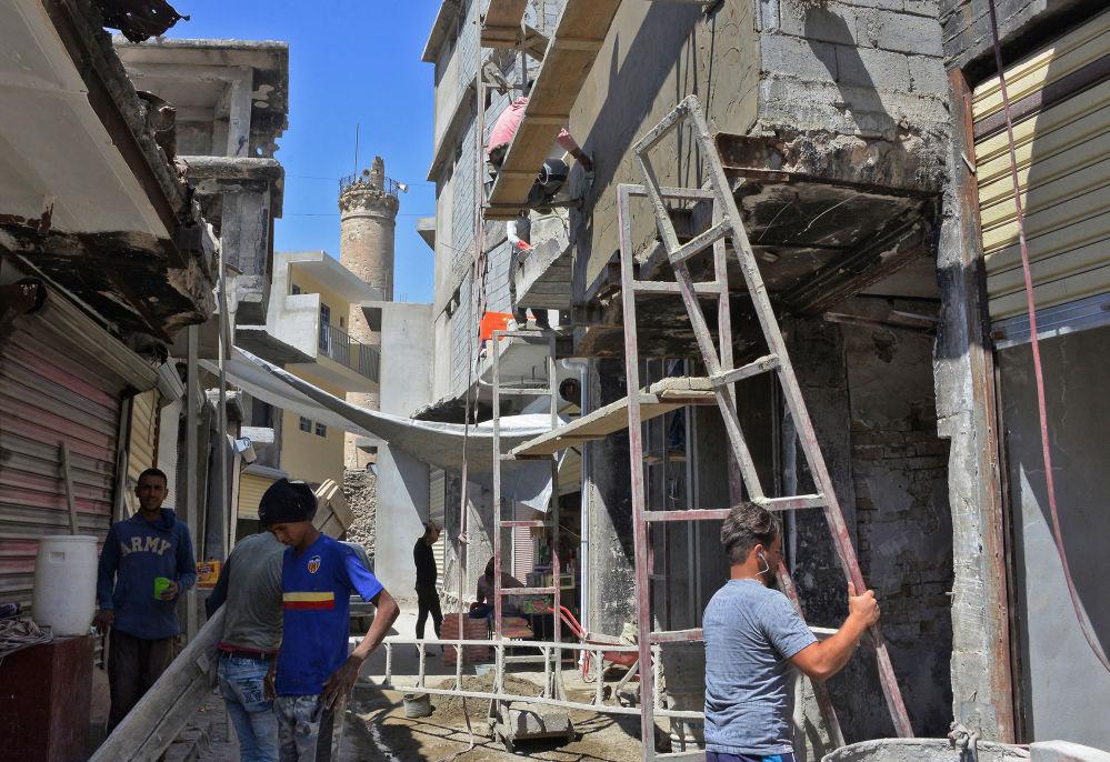 Pracovníci obnovují domy v Mosulu v Iráku v červenci 2018