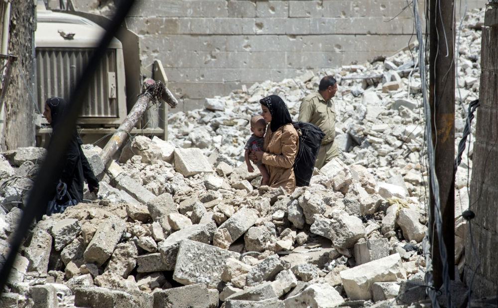 Iracká žena s dítětem mezi zříceninami Starého Města během operace osvobození Mosulu od teroristů IS, červenec 2017