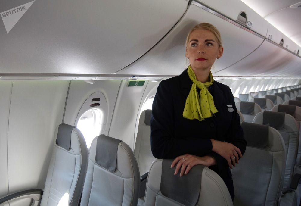Letuška v interiéru letadla Bombardier CS300 lotyšských aerolinek airBaltic