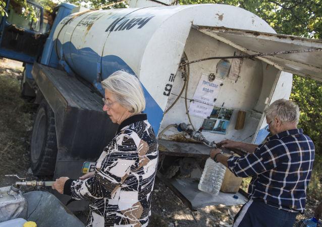 Obyvatelé Luhansku nabírají pitnou vodu do kanistrů