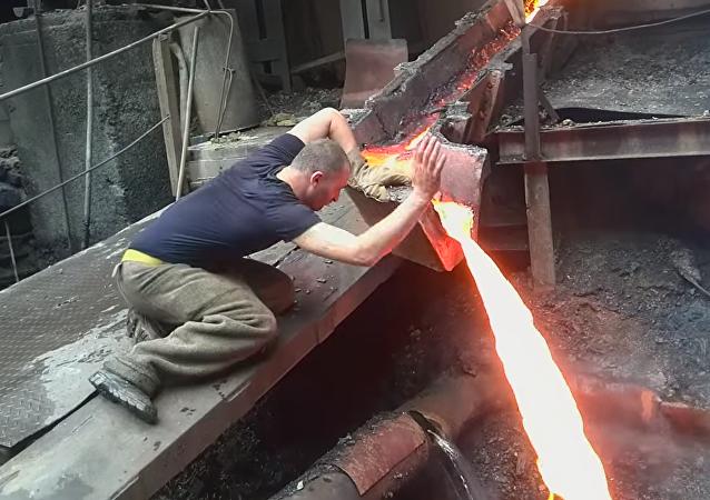 Arménský metalurg strká ruku do roztaveného železa